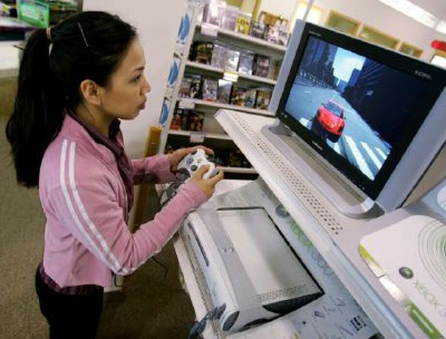 Christine Canasa plays a car racing game with a PC running Microsoft's Windows XP Media Center Edition operating system.