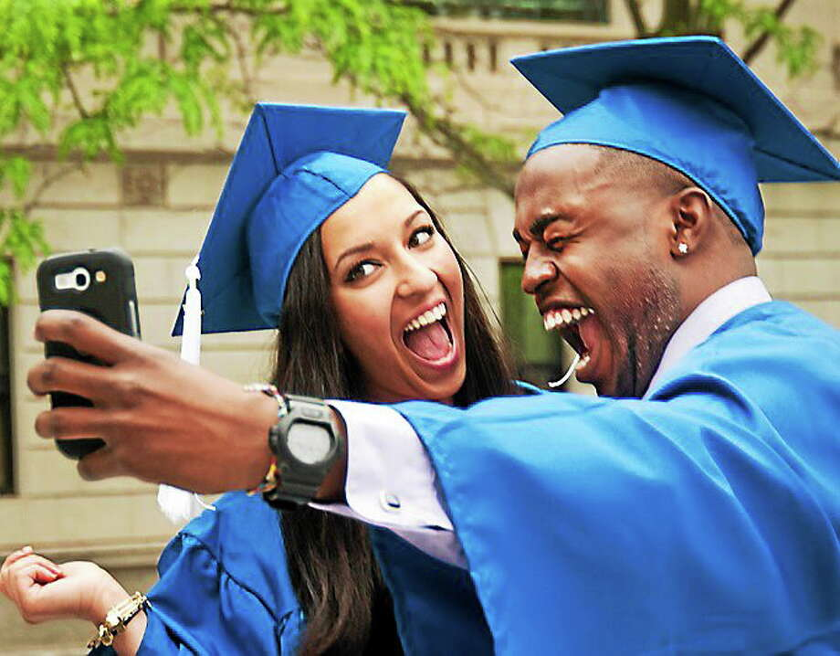 Gateway graduates, Spenta Mehraban (L), and Adon Duncanson, take some selfies before commencement ceremonies at Woolsey Hall 5/22. Photo: Melanie Stengel/New Haven Register