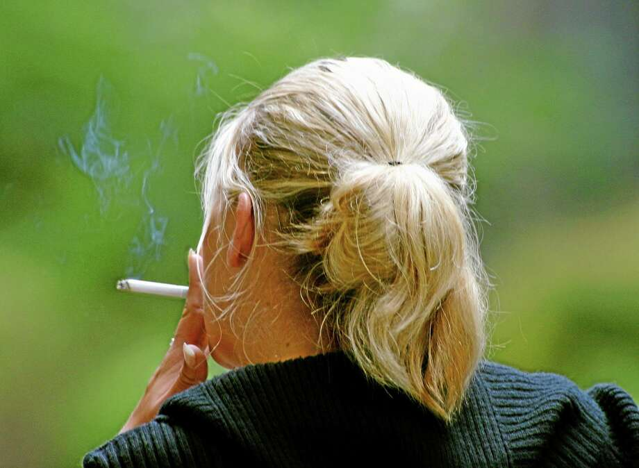 FILE - In this July 20, 2006 file photo, a woman smokes a cigarette during a break from work in downtown Chicago. (AP Photo/Julio Cortez, File) Photo: AP / AP