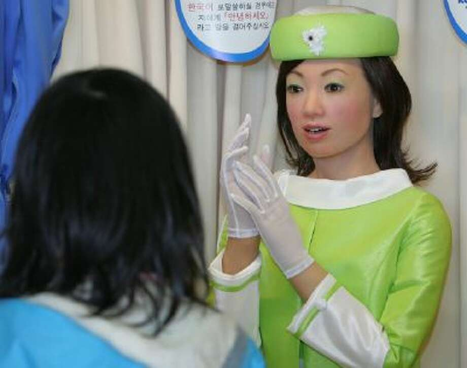"""An information robot called """"Actroid,"""" co-developed by Japan's Kokoro Corp. and Advanced Media Inc., speaks to visitors, working as an official Aichi Expo 2005 multilingual receptionist at West Gate during a press preview of the world fair in Nagakute, central Japan."""