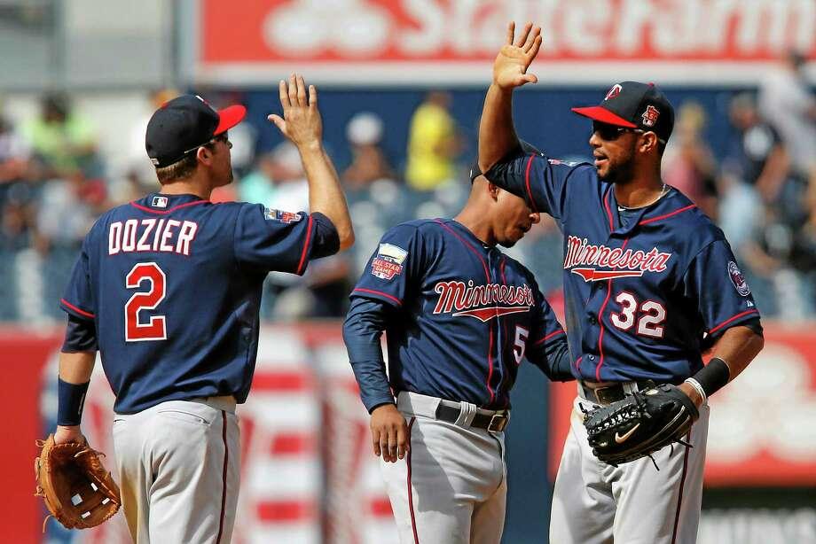 From left, Minnesota Twins' Brian Dozier, Eduardo Escobar and Aaron Hicks celebrate after beat the New York Yankees Sunday. Photo: Jason DeCrow  — The Associated Press   / FR103966 AP