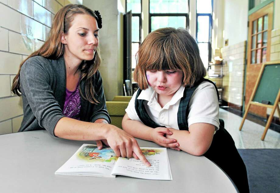 Southern Connecticut State University graduate Amanda Giangrande (left) reads Ms. Turtle the Babysitter with first grader Alexis Martin at St. James School in Stratford on 5/30/2014. Photo: (Arnold Gold-New Haven Register)