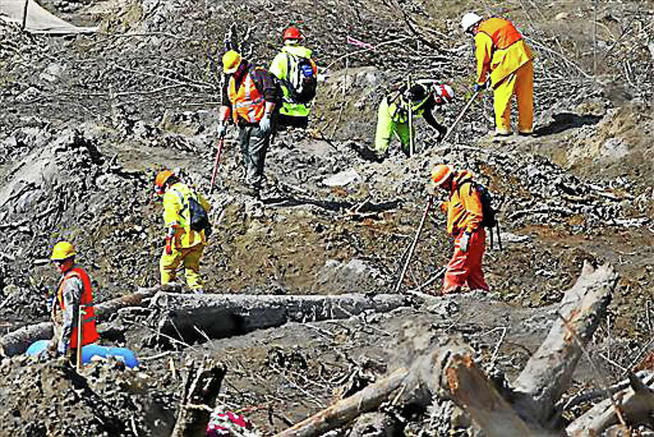 Workers dig at a much drier mudslide site on the west side at the west site of the mudslide on Highway 530 near mile marker 37, near Oso, Wash., on Tuesday, April 1, 2014. The death toll from the March 22 mudslide has increased to 28. (AP Photo/The Seattle Times, Lindsey Wasson)  SEATTLE OUT; USA TODAY OUT; MAGS OUT; TELEVISION OUT; NO SALES; MANDATORY CREDIT TO BOTH THE SEATTLE TIMES AND THE PHOTOGRAPHER Photo: AP / The Seattle Times