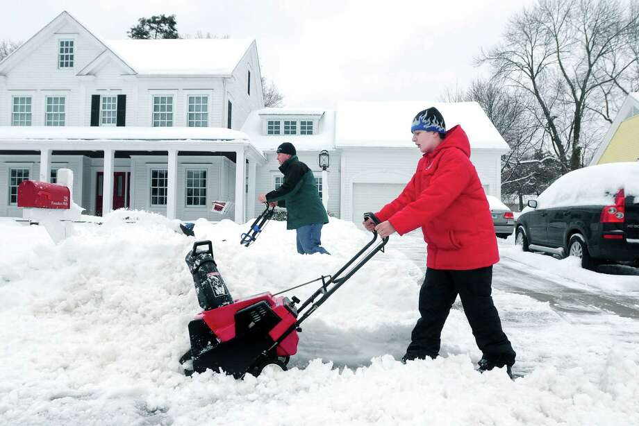 Frank Paine (left) and his son, Frankie (right), 13, clear the snow from a neighbor's driveway and sidewalk in Milford on 2/5/2014. Photo: (Arnold Gold - New Haven Register)