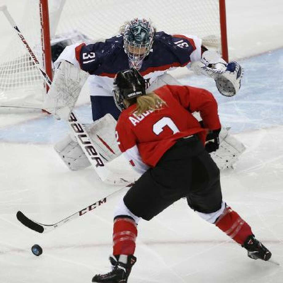 Meghan Agosta-Marciano of Canada shoots toward USA Goalkeeper Jessie Vetter during the first period of the 2014 Winter Olympics women's ice hockey game at Shayba Arena, Wednesday, Feb. 12, 2014, in Sochi, Russia.