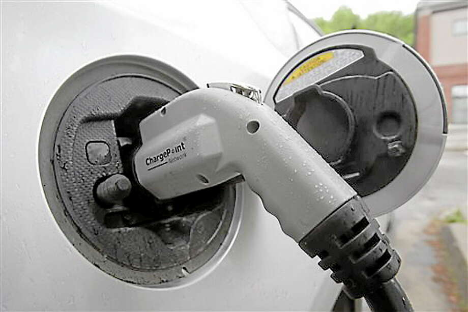 An electric vehicle is attached to a charging station on Tuesday, June 18, 2013 in Montpelier, Vt.  Vermont Gov. Peter Shumlin and Quebec Premier Pauline Marois say they're implementing an electric vehicle charging corridor across the international boundary between the state and province. The corridor will initially link Burlington and Montreal with more than 20 charging stations along the 138-mile route.(AP Photo/Toby Talbot) Photo: AP / AP