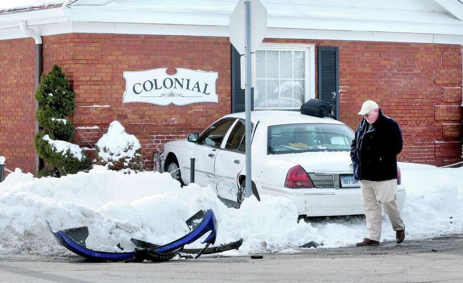 "A car ran into Colonial Funerals on the corner of Circular Ave. and Bradley Ave. in Hamden on 2/12/2014.  Peter Moraski, owner of Colonial Funerals, thinks it's a bad intersection and says, ""they want drive-in service I guess.""  In the foreground is the fender from the other car involved in the accident. Photo: (Arnold Gold - New Haven Register)"