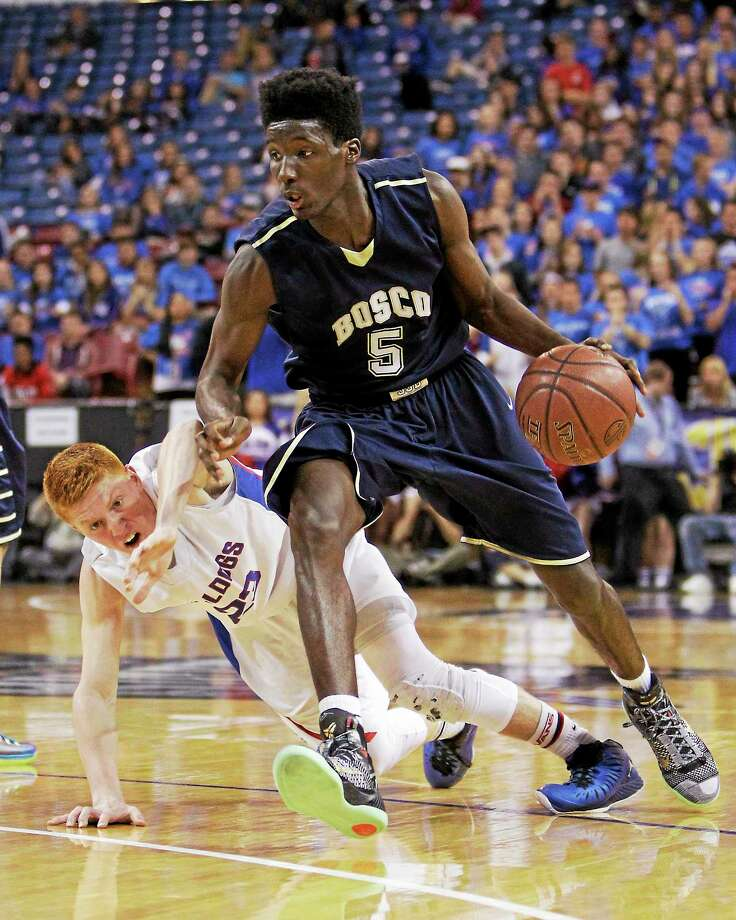 St. John Bosco forward Daniel Hamilton, who is headed to UConn, eludes Folsom guard Jared Wall during the Division 2 CIF championship game on Saturday in Sacramento, Calif. Hamilton scored 22 points as St. John Bosco won 63-54 and then watched the Huskies beat Michigan State on the bus ride back to Los Angeles. Photo: Rich Pedroncelli — The Associated Press   / AP