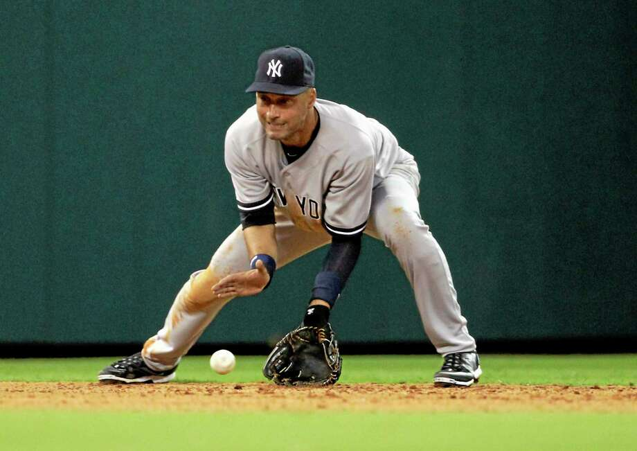 Yankees shortstop Derek Jeter misses a grounder hit by the Houston Astros' Chris Carter during the eighth inning of Tuesday's game. The Yankees lost 6-2. Photo: Patric Schneider  — The Associated Press   / FR170473 AP
