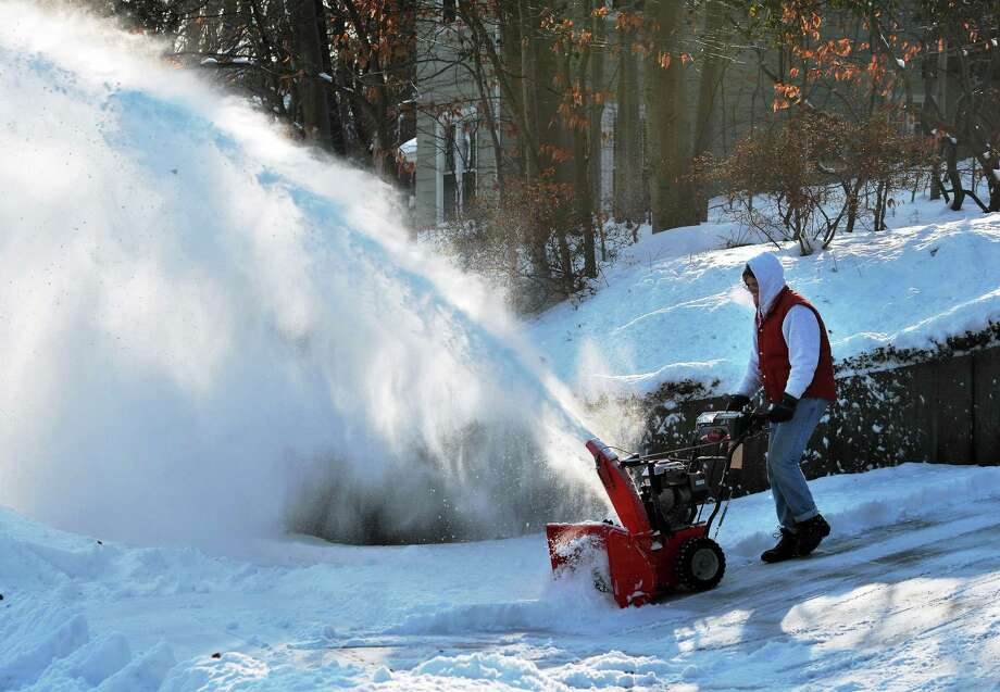 Will Keyes of New Haven helps clear snow off a neighbor's driveway along Hemlock Road in New Haven in January 2014. Photo: Peter Casolino — New Haven Register