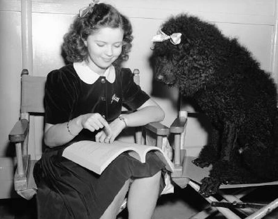 Shirley Temple studies a script with Fifi, a dog cast alongside her, on Sept. 12, 1941.