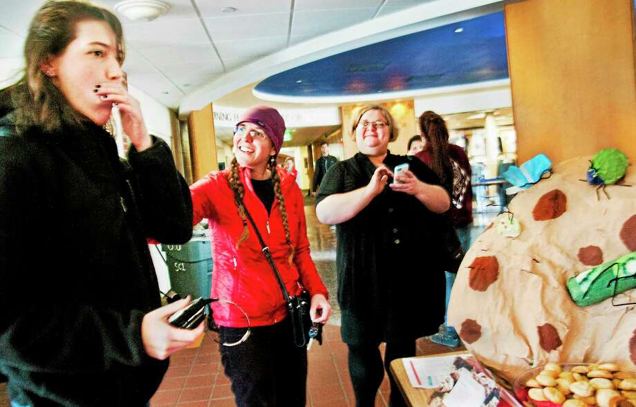 Quinnipiac University freshman Stephane Buechel, left, tries not to think about the crickets in the cookie that she's eating Tuesday. Congratulating Buechel on her bravery is anthropology professor Hillary Haldane. At right is anthropology professor Jaime Ullinger. Photo: Melanie Stengel — New Haven Register      / PETER HVIZDAK