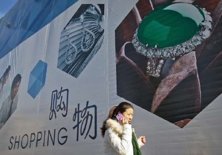 A woman talks on her mobile phone as she walks past an advertisement billboard for a new shopping mall in Beijing.