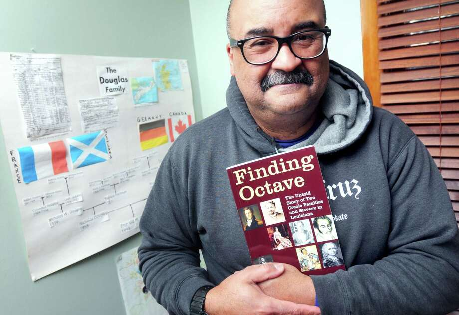 """Nick Douglas holds his book, """"Finding Octave, The Untold Story of Two Creole Families and Slavery in Louisiana,"""" at his home in North Branford on 2/10/2014.  Behind him is a family tree created by his daughter, Emerald, when she was 14. Photo: (Arnold Gold - New Haven Register)"""