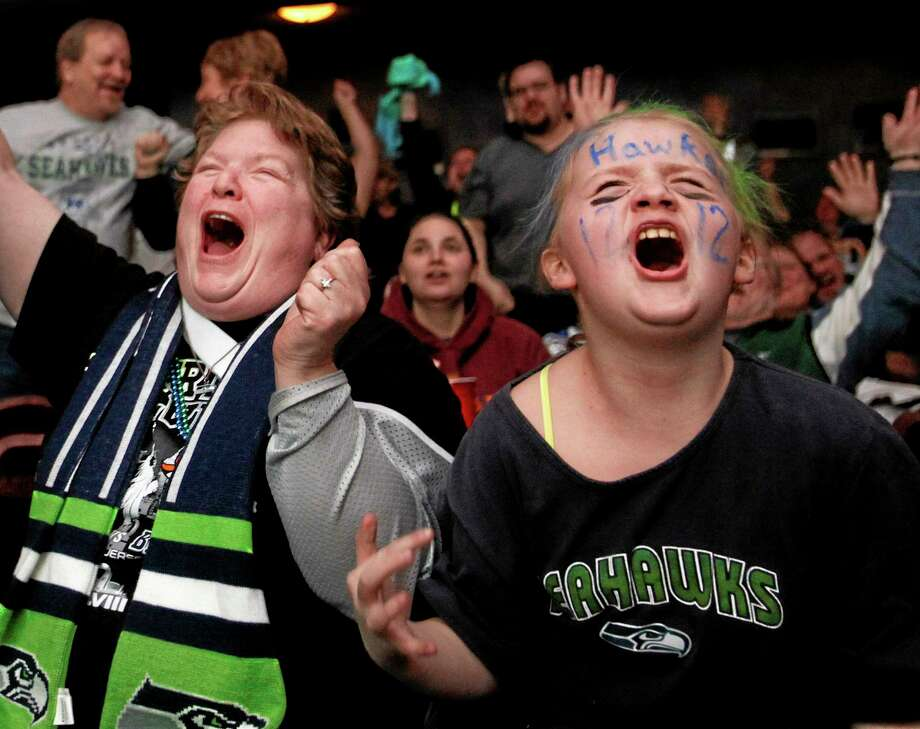 Annicka and Janet Pollack celebrate as the Seattle Seahawks score a touch down during the third quarter of the Super Bowl XLVIII at a Superbowl party at the Historic Everett Theatre Sunday, Feb. 2, 2014 in Everett, Wash. (AP Photo/ The Herald, Sofia Jaramillo) Photo: AP / THE HERALD
