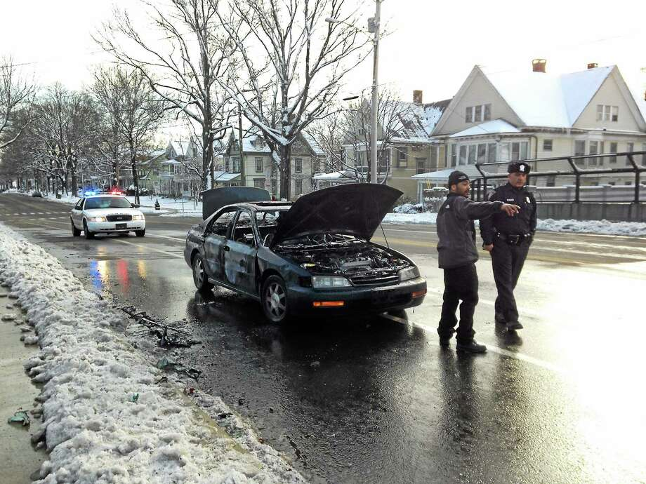 A Honda Accord caught fire on Howard Avenue. Rob Miller, whose wife was driving the Honda when it began to smoke and then caught fire, points to his home, just blocks away. Photo: Mercy Quaye — New Haven Register
