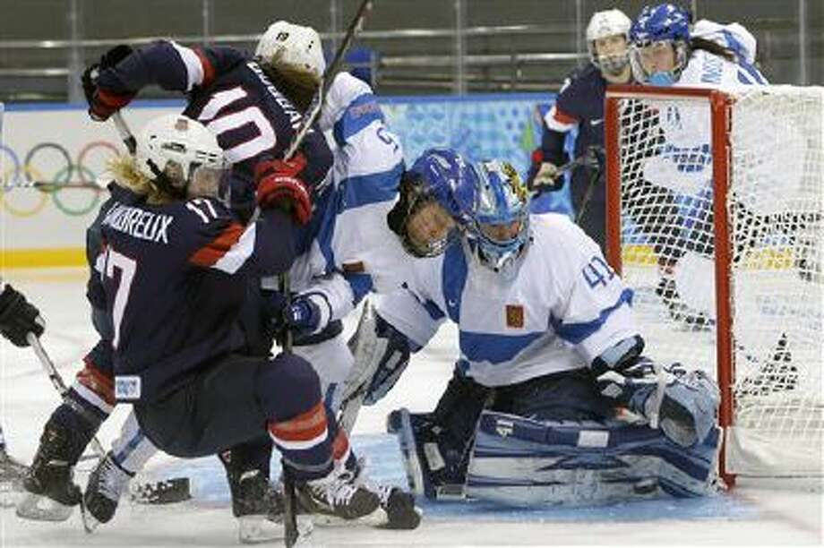 Goalkeeper Noora Raty of Finland reaches for the puck as Anna Kilponen of Finland (5) keeps Meghan Duggan of the Untied States (10) and Jocelyne Lamoureux of the Untied States (17) away from the gaoll during the third period of the women's ice hockey game at the Shayba Arena during the 2014 Winter Olympics, Saturday, Feb. 8, 2014, in Sochi, Russia. Photo: AP / AP