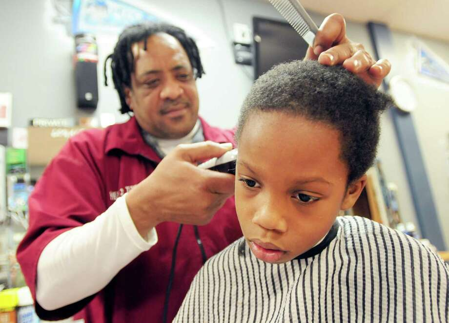 Bryshon Reaves of New Haven, 9, gets a free haircut from barber Cleveland Murray at Head 2 Toe barbershop in New Haven courtesy of the Sports Academy of New Haven. Photo: Peter Hvizdak — New Haven Register      / ©Peter Hvizdak /  New Haven Register