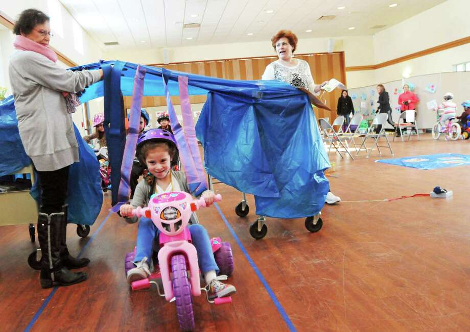 (Photo by Peter Hvizdak ó New Haven Register)  Edie Slossberg, a Temple Beth Sholom congregant and K'tanim Nursery School music teacher, left, and Ina Gross, right, hold up the curtain of a simulated car wash on a bike path  for K'tanim Nursery School pre-schooler Lilly Messina, 5, Tuesday morning February 4, 2014 at the Hamden school as the preschoolers ride bicycles to raise money for St. Jude Children's Research Hospital. Ina Gross is Lilly Messina's daughter. Photo: New Haven Register / ©Peter Hvizdak /  New Haven Register