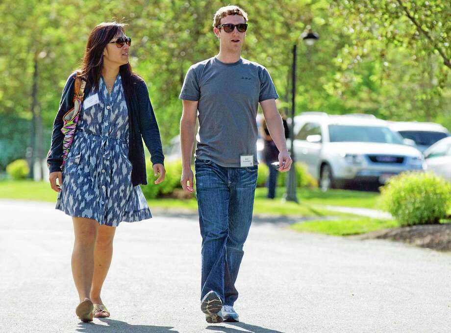 FILE - In this July 9, 2011, file photo, Mark Zuckerberg, president and CEO of Facebook, walks with Priscilla Chan during the 2011 Allen and Co. Sun Valley Conference, in Sun Valley, Idaho. Zuckerberg and his wife, Chan, were the most generous American philanthropists in 2013, The Chronicle of Philanthropy reported, Monday, Feb. 10, 2014, with a donation of 18 million Facebook shares, valued at more than $970 million, given to a Silicon Valley nonprofit in December. (AP Photo/Julie Jacobson, File) Photo: AP / AP