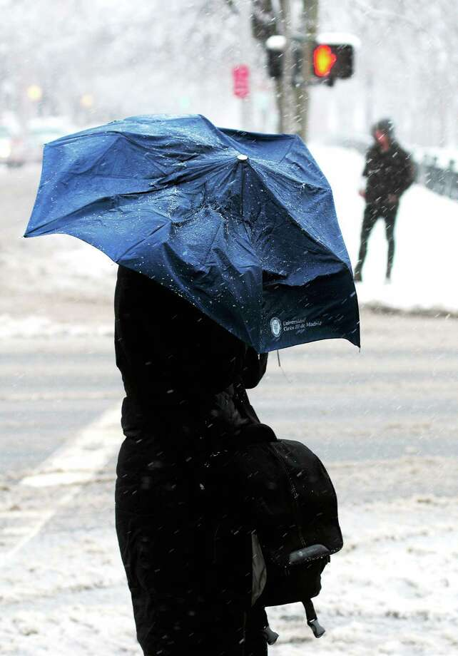 A woman shields herself from the snow crossing College St. in New Haven on 2/3/2014. Photo: (Arnold Gold - New Haven Register)