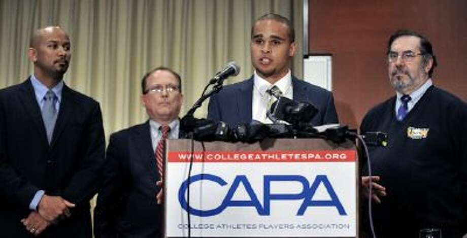 Northwestern quarterback Kain Colter second from right, speaks while College Athletes Players Association president Ramogi Huma left, United Steel Workers National Political Director Tim Waters second from left, and United Steel Workers president Leo Gerard right, look on during a news conference in Chicago, Tuesday.