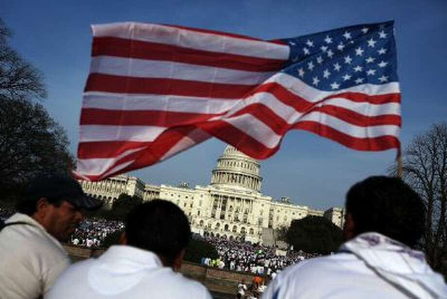 Immigration reform activists wave an American flag at a protest on the U.S. Capitol. Here's why immigration reform is difficult. Photo: Getty Images / 2013 Getty Images