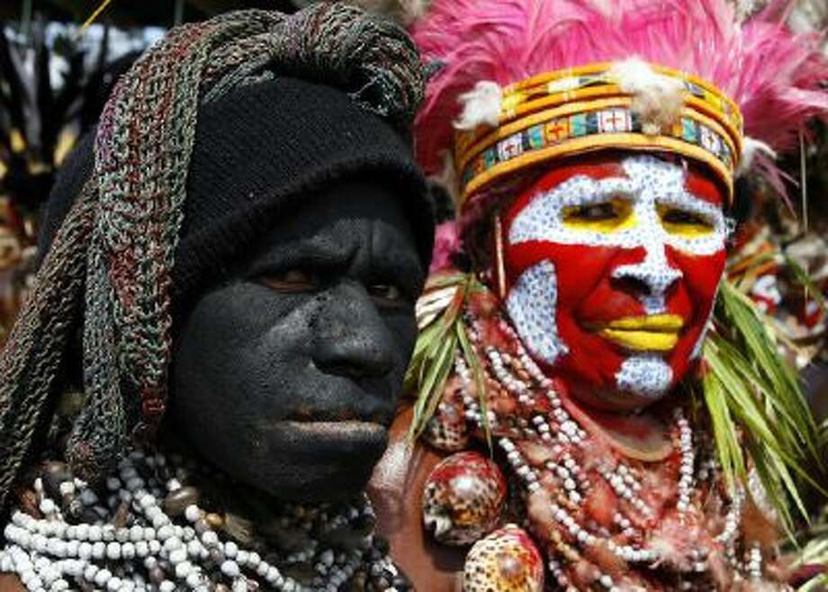 A Southern Highlands woman mourning her dead husband (L) and a Western Highlands woman (R), both wearing necklaces of Job's tears, watch the 50th Goroka singsing (cultural show) from the stands in what is believed to be the largest gathering of indigenous tribes in the world, 17 September 2006. Over 90 tribes from all over Papua New Guinea -- the world's most culturally diverse nation -- have gathered in Goroka for the annual festival of traditional dance.