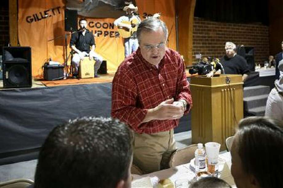 In this photo taken Saturday, Jan. 11, 2014, U.S. Sen. Mark Pryor, D-Ark., speaks to people at the Gillett Coon Supper in Gillett, Ark., as a band plays on a nearby stage. Photo: AP / AP