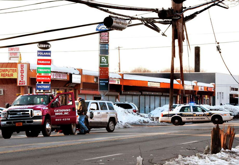 A vehicle is towed from Ella Grasso Boulevard where it overturned and severed a utility pole Monday in New Haven. Photo: Melanie Stengel — New Haven Register   / PETER HVIZDAK