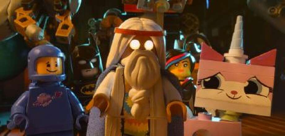 "This image released by Warner Bros. Pictures shows characters, from left, Benny, voiced by Charlie Day, Batman, voiced by Will Arnett, Vitruvius, voiced by Morgan Freeman, Wyldstyle, voiced by Elizabeth Banks and Unikitty, voiced by Alison Brie, in a scene from ""The Lego Movie."""