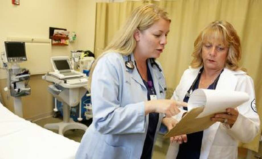 Nurse practitioners Michele Knappe, left, and Julie Zimmer go over a patient's chart at Ingalls Family Care Center in Flossmoor, Ill. The need for health care workers is expected to surge in the next decade, and several governors are pushing proposals designed to attract more qualified applicants. / AP2013