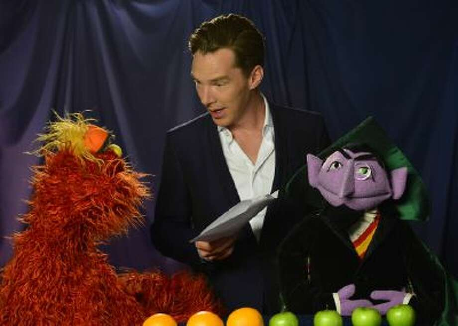 """This image released by Sesame Workshop shows characters Murray Monster, left, and Count von Count, right, with actor Benedict Cumberbatch during the taping of a video for """"Sesame Street,"""" posted Tuesday, Feb. 4, 2014, on PBS' YouTube channel. With the help of Count and Murray, Cumberbatch explains how to count up four apples and three oranges, and which is the greater number."""