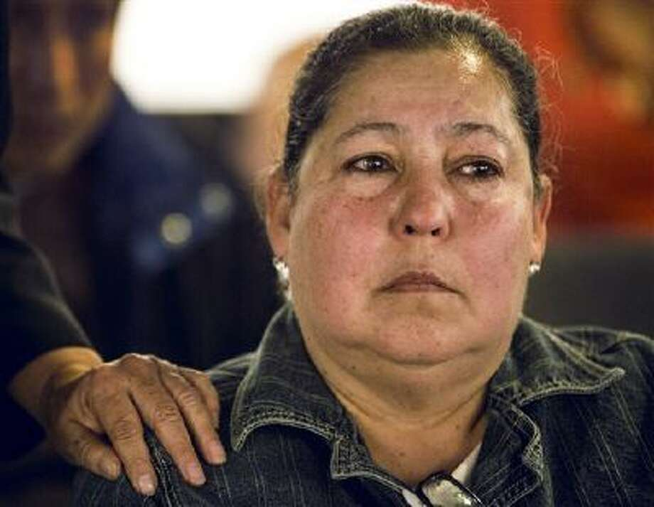 Rosa Maria Camorlinga, whose son Israel Camirlinga recently was deported to Mexico, listens to Sen. Ronald Calderon, D-Calif., as he speaks on immigration. Photo: AP / AP