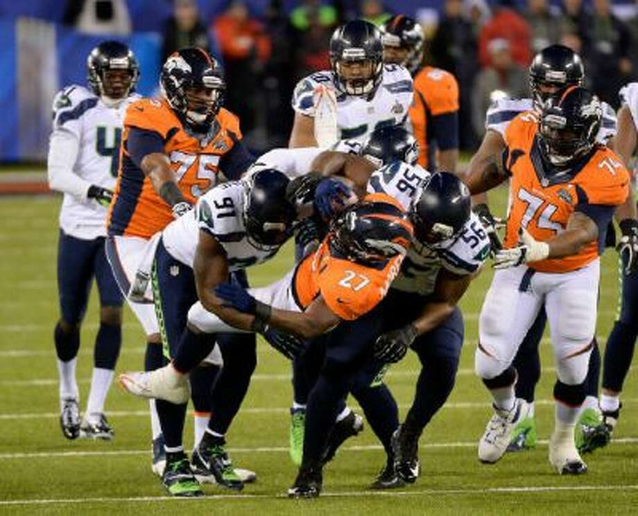 Denver Broncos running back Knowshon Moreno (27) gets hit hard during the first quarter. The Denver Broncos vs the Seattle Seahawks in Super Bowl XLVIII at MetLife Stadium in East Rutherford, New Jersey Sunday.