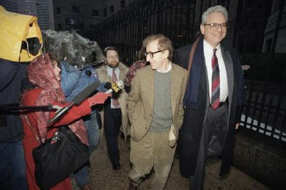 This Jan. 12, 1993 photo shows director Woody Allen trading grins with a pursuing television reporter as he arrives at State Supreme Court in Manhattan, New York.