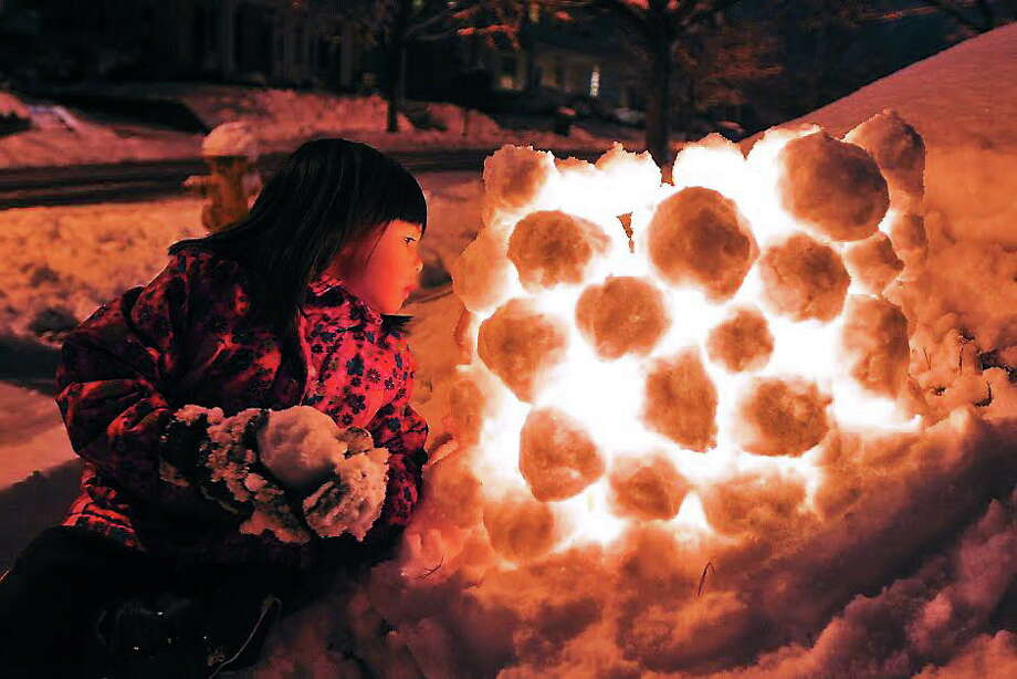 Maia Sindelar, 4, looks at a candle inside a snow sculpture made by a neighbor along Hemlock Road in New Haven early Monday evening. 2/3/2014.  pcasolino@NewHavenRegister Photo: (Peter Casolino - New Haven Register)