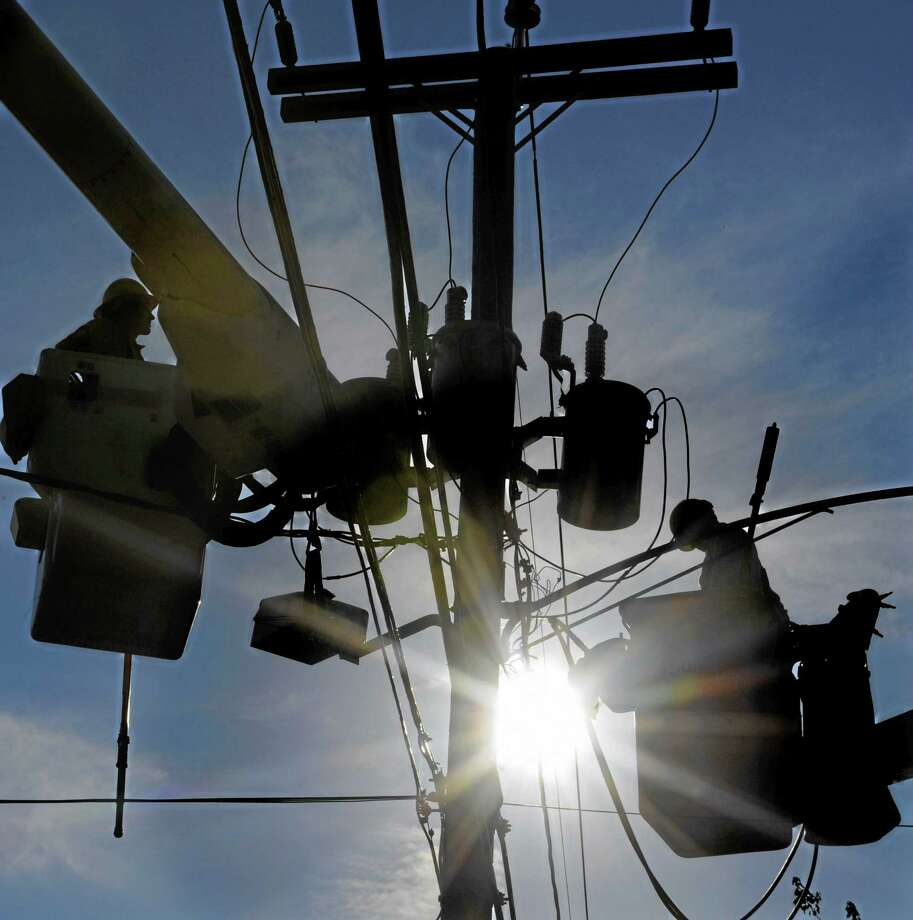 In this Aug. 3, 2011, photo, crews from Connecticut Light and Power replace a damaged transformer in East Windsor in the aftermath of Tropical Storm Irene. Photo: Jessica Hill — The Associated Press   / FR125654 AP