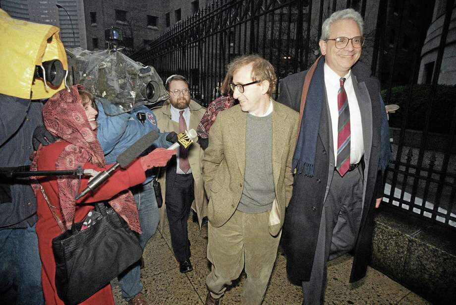 This Jan. 12, 1993 file photo shows director Woody Allen trading grins with a pursuing television reporter as he arrives at State Supreme Court in Manhattan, New York, for a hearing in which he requested more liberal visitation rights with his children during his ongoing dispute with ex-lover actress Mia Farrow. AP Photo/Mario Cabrera Photo: AP / AP
