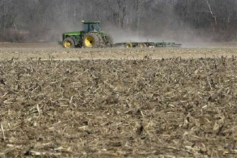 In this photo taken Thursday, Jan. 30, 2014, a farmer takes advantage of dry weather to till a field in preparation for spring planting near England, Ark. A new farm bill that could become law as soon as next week would require a choice between different subsidy approaches that require producers to suffer losses before they can get payouts. (AP Photo/Danny Johnston) Photo: AP / AP