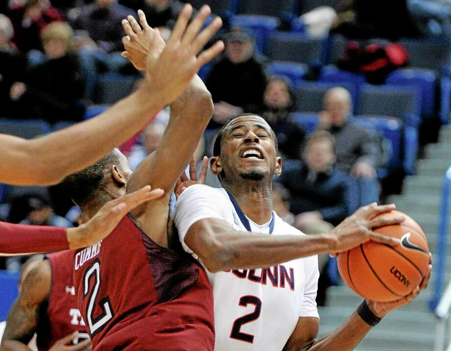 Connecticut's DeAndre Daniels, right, drives past Temple's Will Cummings (2) during the first half of an NCAA college basketball game in Hartford, Conn., Tuesday. Jan. 21, 2014. (AP Photo/Fred Beckham) Photo: AP / FR153656 AP