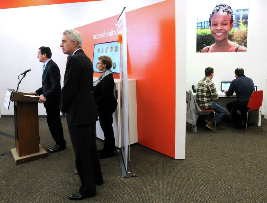 From left, Gov. Dannel P. Malloy; Kevin Counihan, CEO of Access Health CT; and Julia Santos of West Haven, who spoke about her health care experience, attend a press conference in the New Haven Enrollment Center Monday. Photo: Mara Lavitt — New Haven Register     / Mara Lavitt