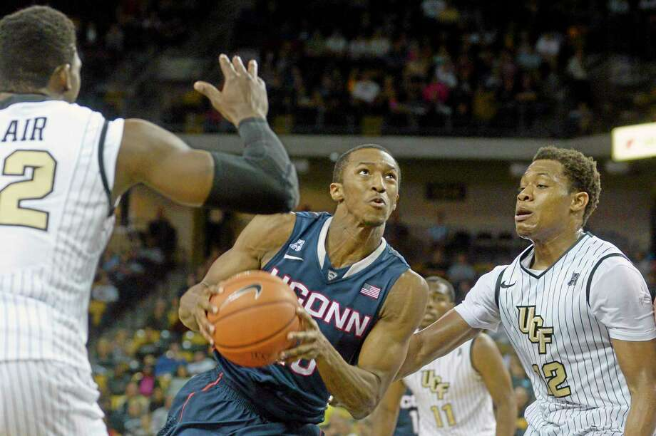 UConn forward Lasan Kromah, center, drives to the basket between Central Florida forward Staphon Blair, left, and Matt Williams during the second half Sunday. Photo: Phelan M. Ebenhack — The Associated Press   / FR121174 AP