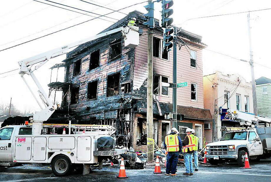 Utilities disconnect any remaining wires from burned building. Photo: Photos By Arnold Gold/Register