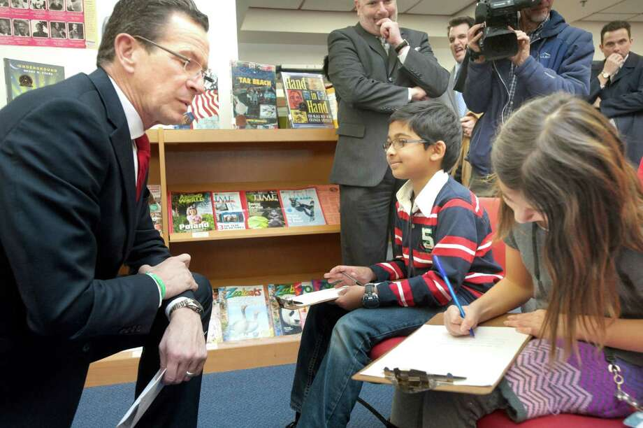 Gov. Dannel P. Malloy answers questions from Helen Street School newspaper reporters fifth-grader Faiz Faroque and fourth-grader Lilly Iocca prior to the start of his press conference at the Hamden school Friday. Photo: VM Williams — New Haven Register