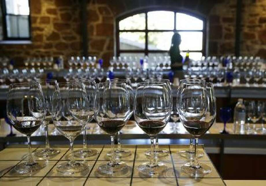 A server fills glasses in preparation for a 10-year vertical tasting of Joseph Phelps Insignia wine at Flavor! Napa Valley at the Culinary Institute of America Saturday, Nov. 23, 2013, in St. Helena, Calif.