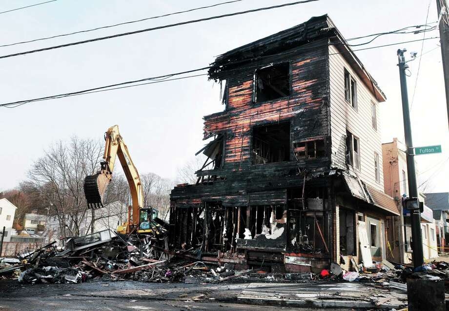 (Arnold Gold ó New Haven Register)  The fire-damaged, multifamily home at corner of Farren Avenue and Fulton Street in New Haven is demolished on Saturday afternoon. Photo: Journal Register Co.