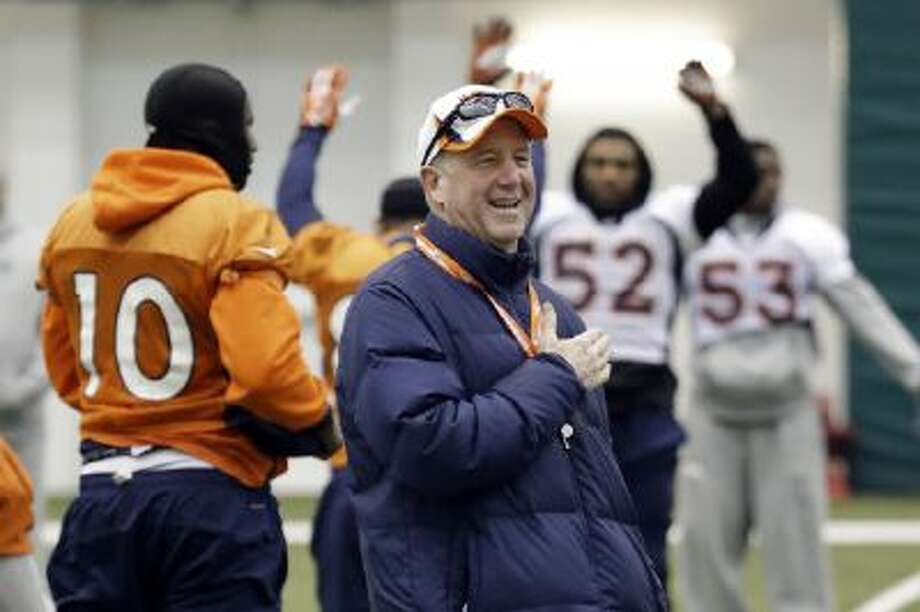 Denver Broncos head coach John Fox talks with players as they stretch during practice Friday in Florham Park, N.J.