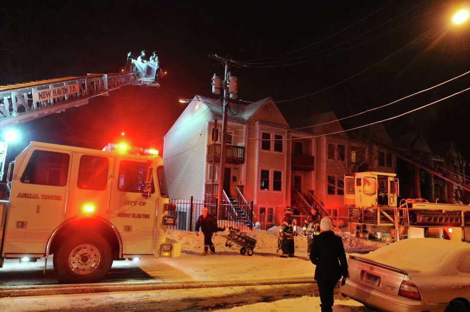 Firefighters battle a two-alarm fire on Henry Street in New Haven Sunday night. 2/9/14. Photo: Peter Casolino/New Haven Register