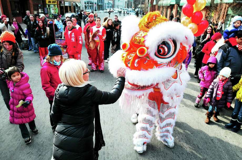 (Arnold Gold ó New Haven Register)  Edie Mauer of New York City pets the lion during a lion dance at Lunarfest, a celebration of the Chinese New Year, on Whitney Ave. in New Haven on 2/1/2014. Photo: Journal Register Co.